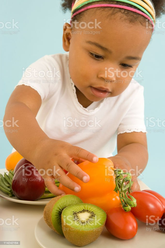 Young girl chooses healthy fruit and vegetables stock photo