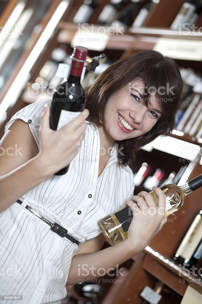 young girl chooses wine in a supermarket stock photo