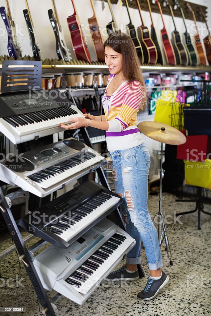 Young girl choosing synthesizer stock photo