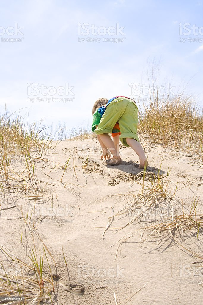 Young girl climbing a small sand dune stock photo
