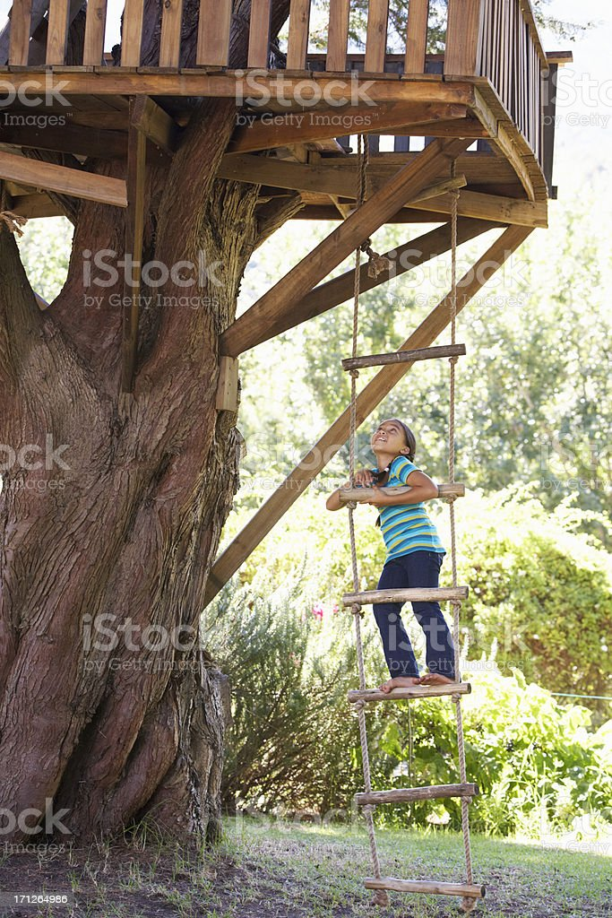 Young Girl Climbing Rope Ladder To Treehouse stock photo