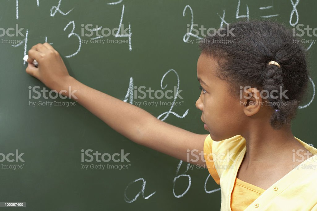 Young girl completing sums on a blackboard stock photo