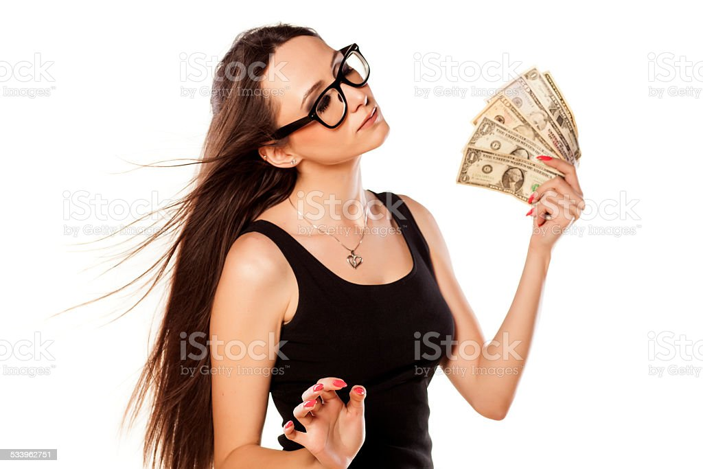 Young girl cooling herself with a fan of money stock photo