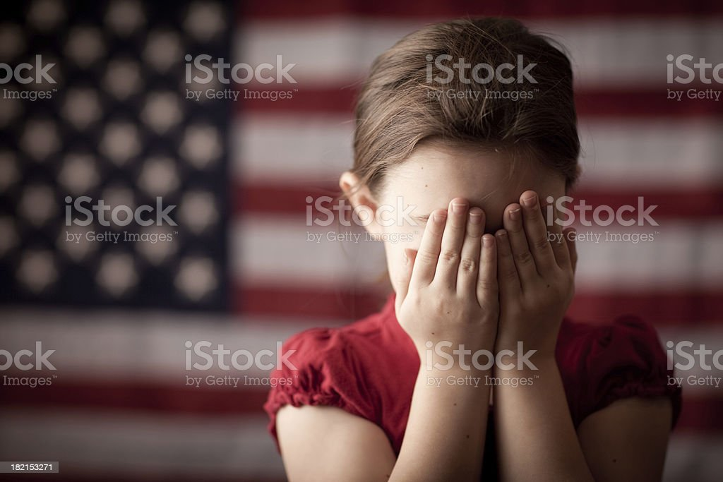 Young Girl Covering Her Face in Front of American Flag royalty-free stock photo
