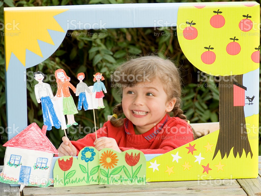 Young girl creating a play with a home-made theatre royalty-free stock photo