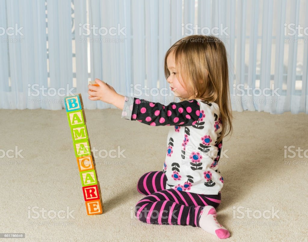 Young girl creating Obamacare tower from wood blocks stock photo