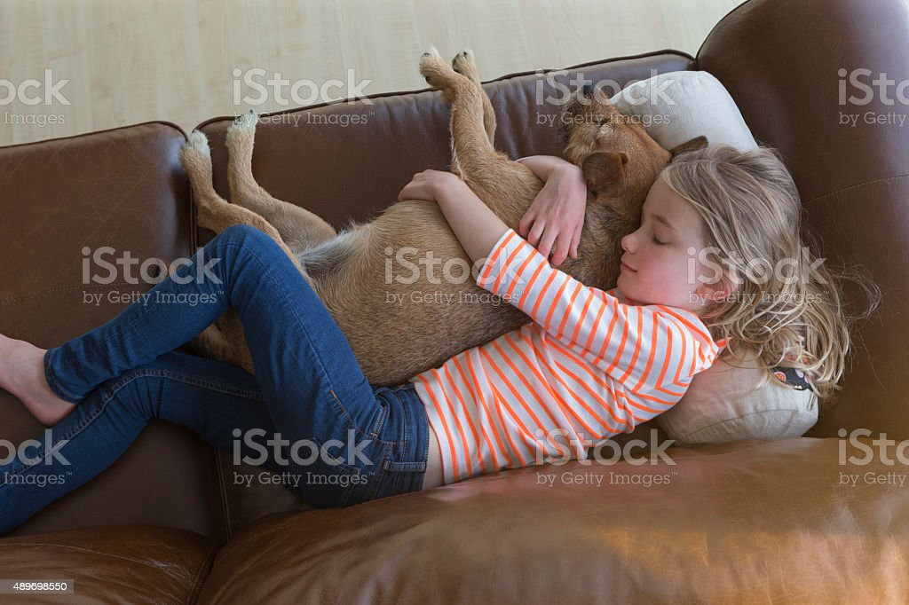 Young girl cuddling her pet dog at home stock photo