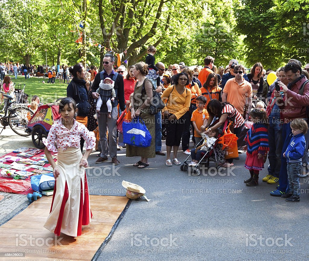 Young girl dances in the Vondelpark during Queen' s Day stock photo