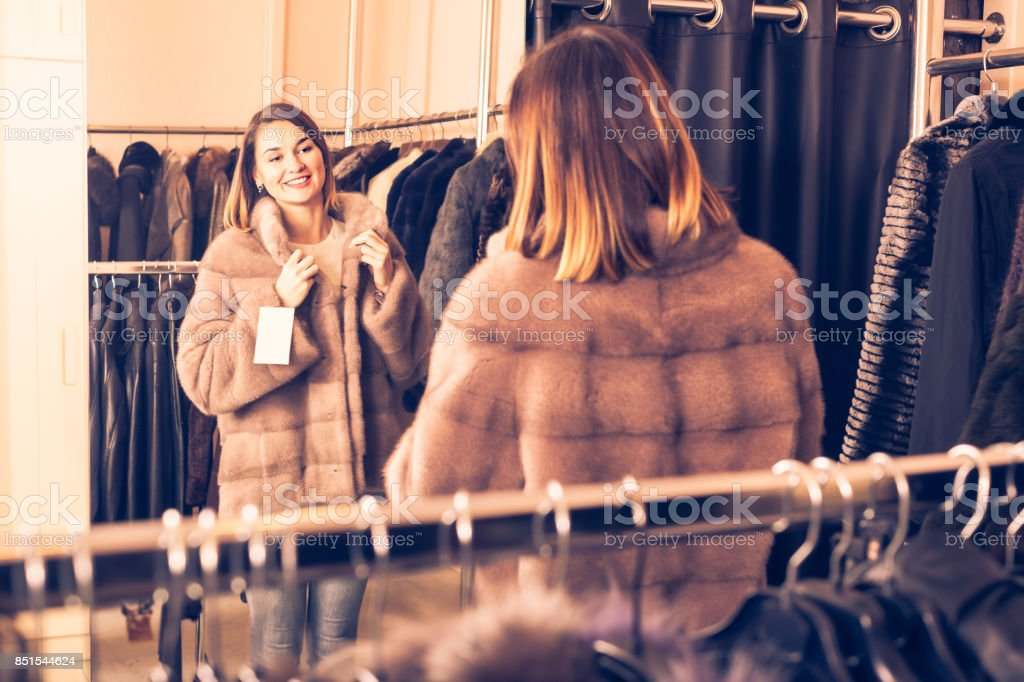Young girl deciding on the choice of fur coat stock photo