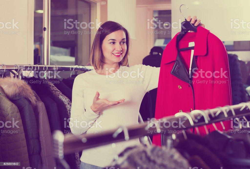 Young girl deciding on warm red coat stock photo