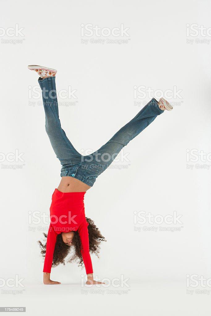 Young girl doing cartwheel indoors stock photo