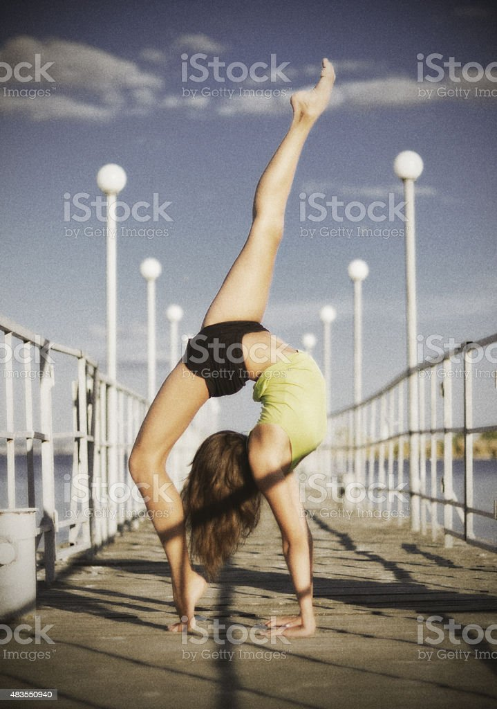 Young girl doing gymnastic exercises on the pier (ancient ver) stock photo