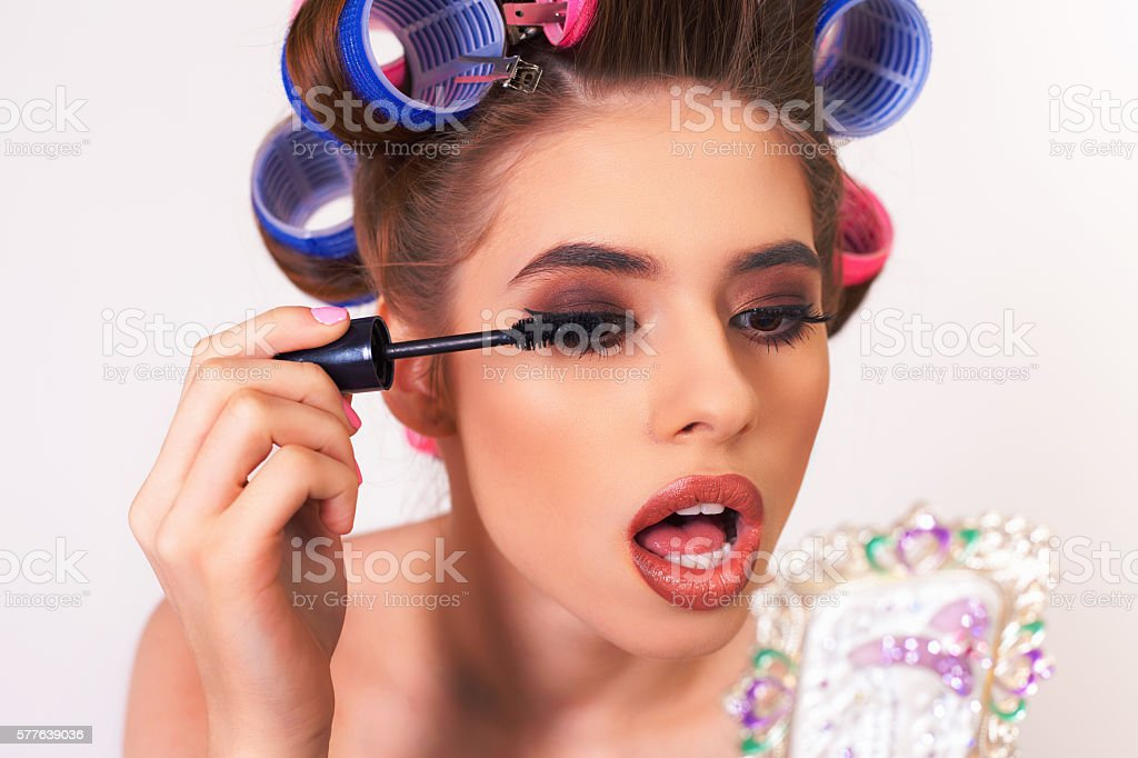 Young girl doing makeup and hairstyle using curlers stock photo