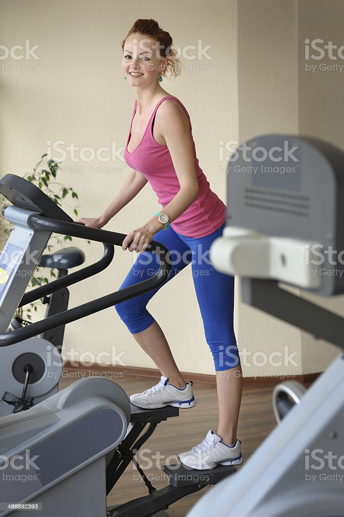 young girl doing step machine workout stock photo