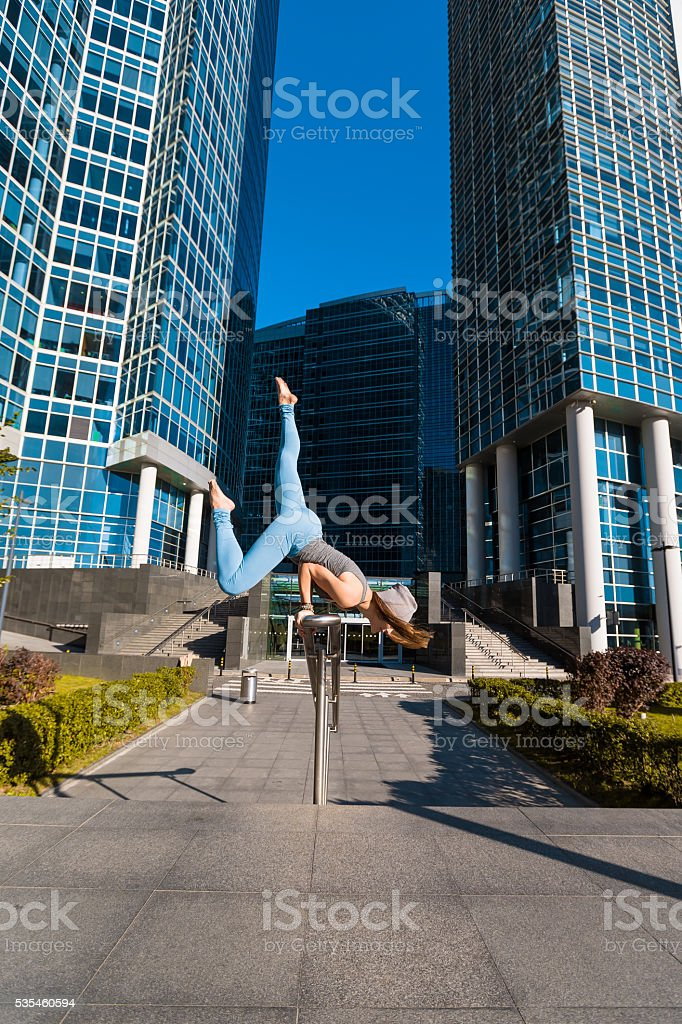 Young girl doing yoga outdoors in city stock photo