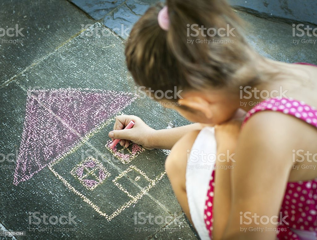 Young girl drawing a hose in chalk on the sidewalk stock photo