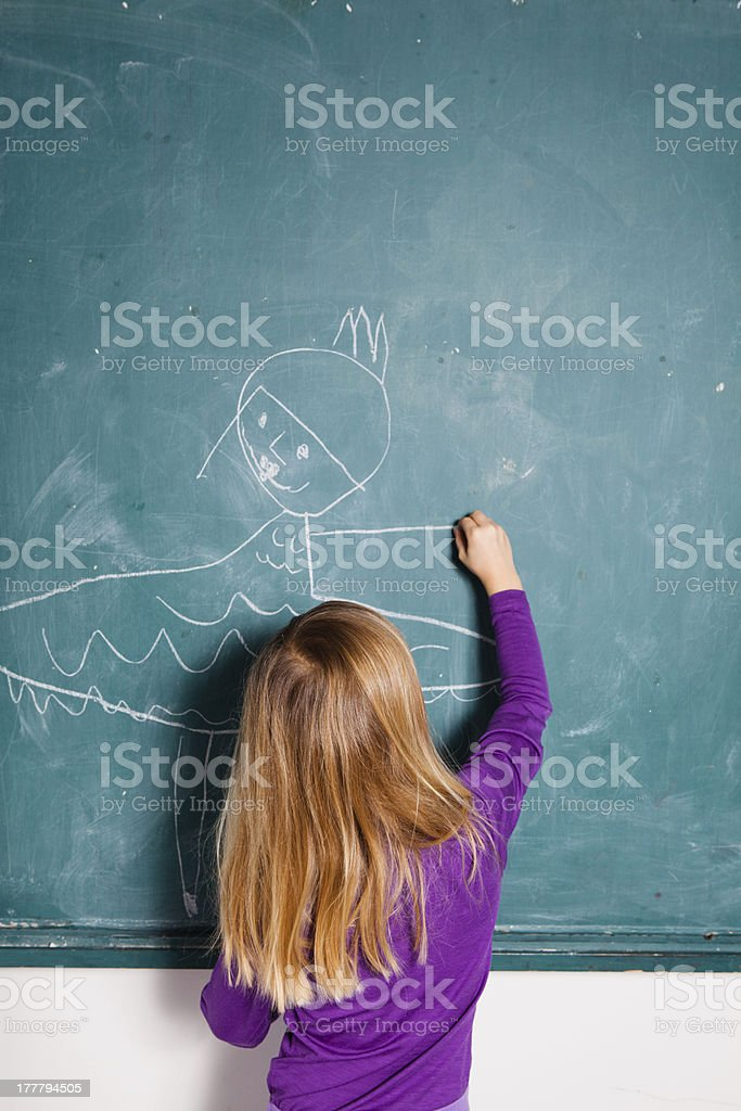 Young girl drawing on chalkboard royalty-free stock photo