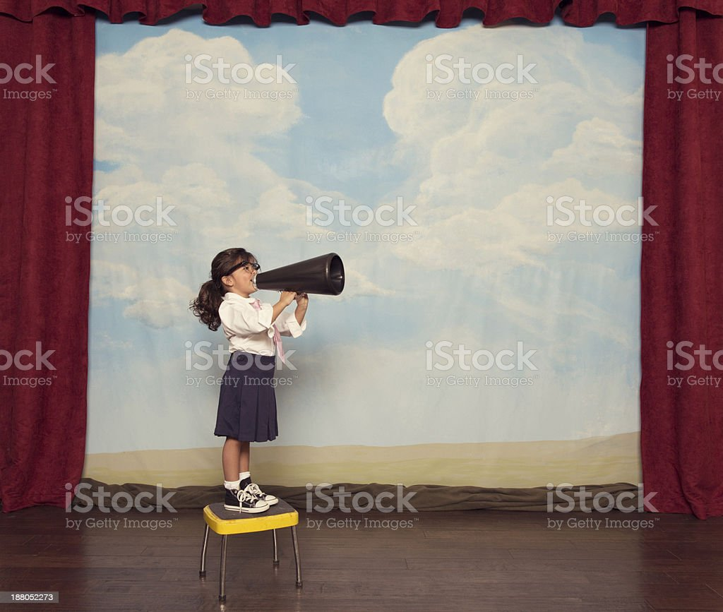 Young Girl Dressed as Businesswoman Yells Through Megaphone stock photo