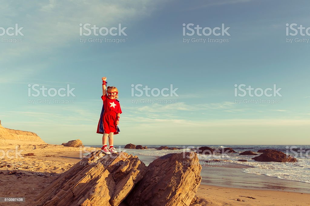 Young Girl dressed as Superhero on California Beach stock photo
