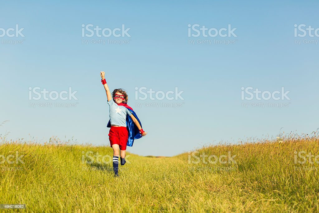 Young Girl dressed as Superhero Running in Grass stock photo