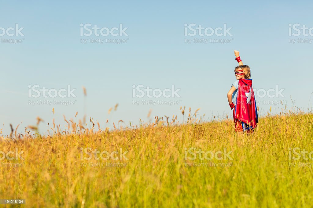 Young Girl dressed as Superhero Standing in Grass stock photo