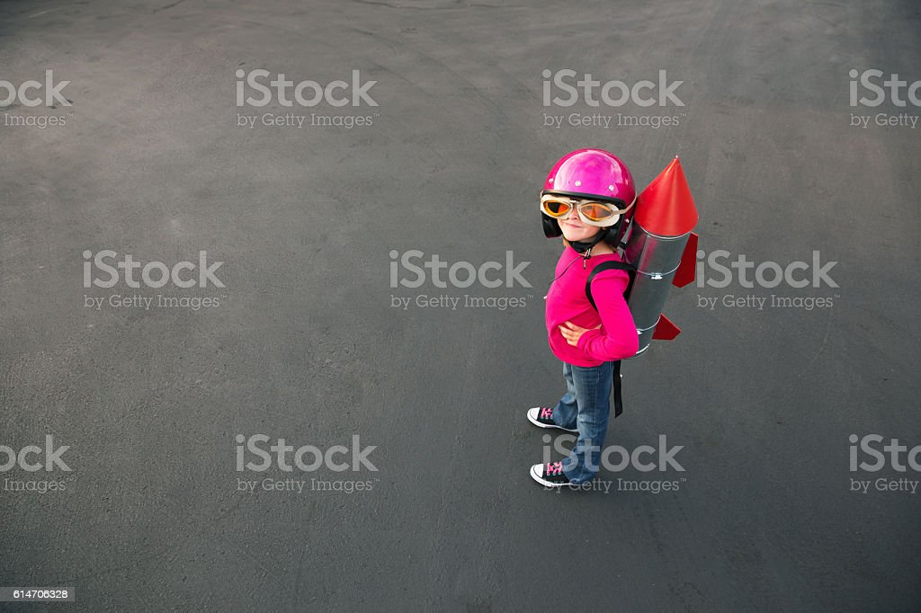 Young girl dressed in a red rocket suit on blacktop stock photo