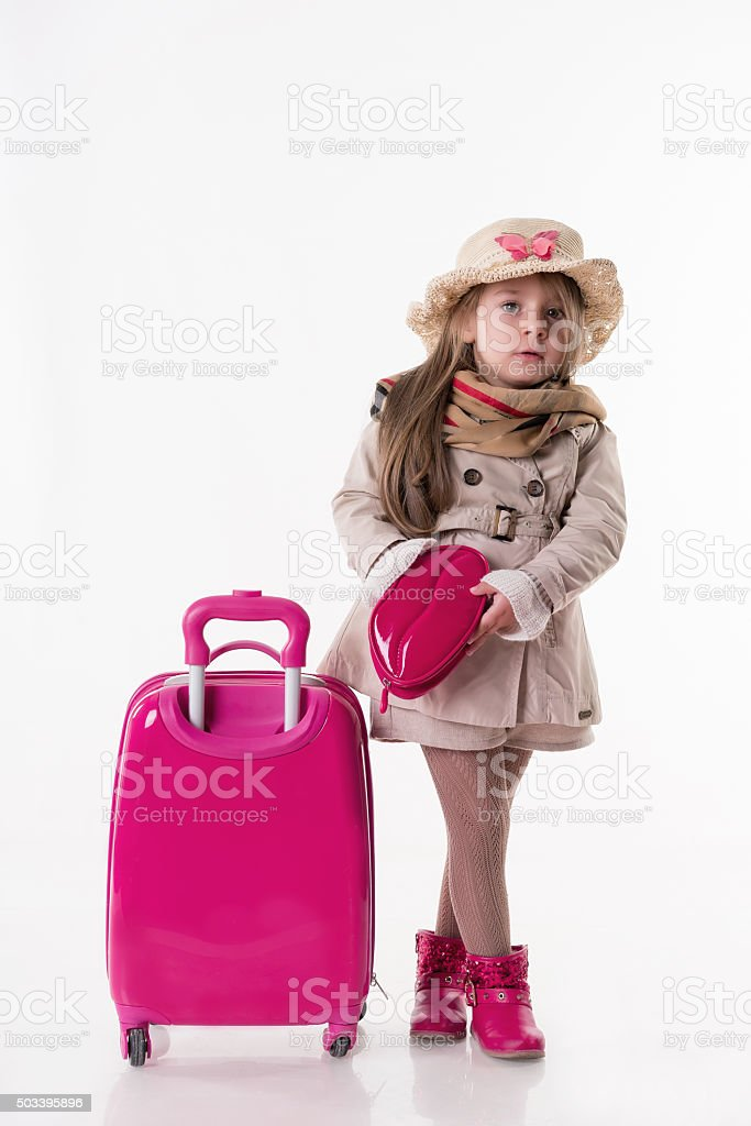 Young girl dressed in holiday clothes pulling suitcase stock photo