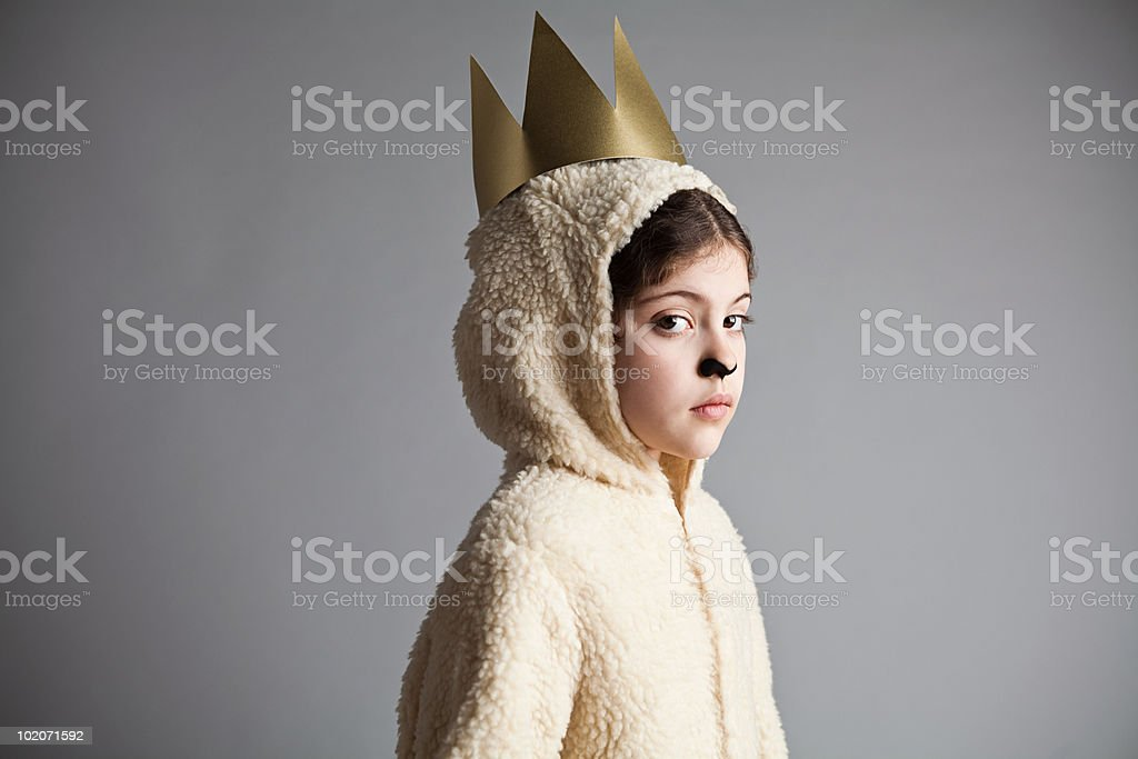 Young girl dressed up as sheep, wearing gold crown stock photo