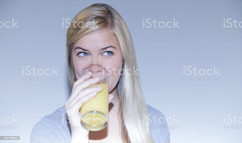 Young girl drinking a glass of orange juice royalty-free stock photo