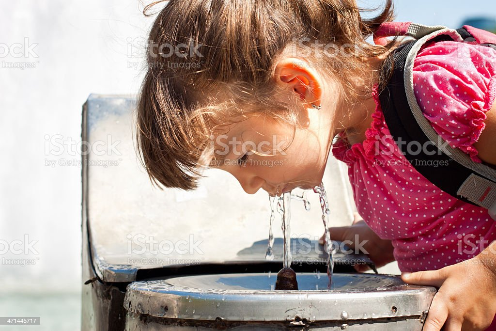 Young girl drinking from a water fountain stock photo