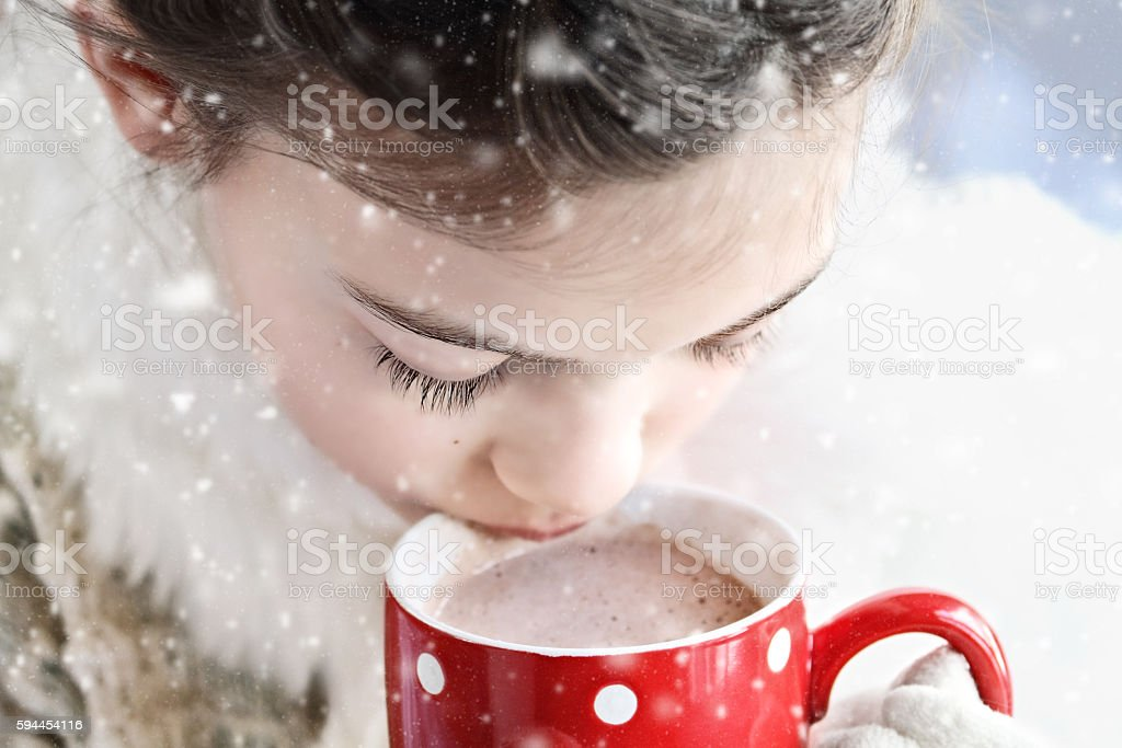 Young girl drinking hot chocolate outdoor stock photo