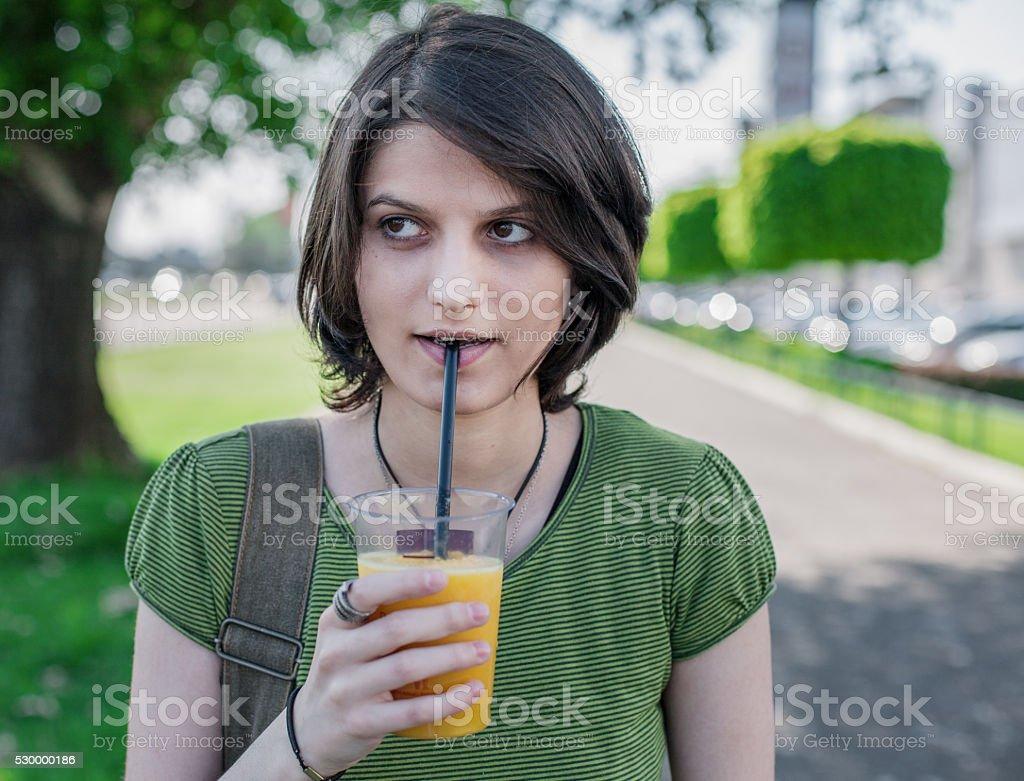 Young girl drinking orange smoothie royalty-free stock photo