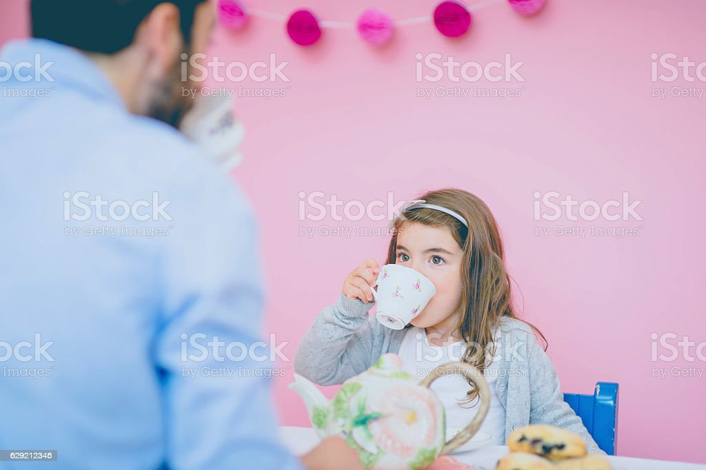 Young girl drinking tea during tea party with dad stock photo