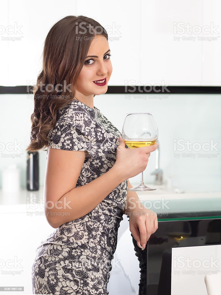 Young girl drinking vine in kitchen stock photo
