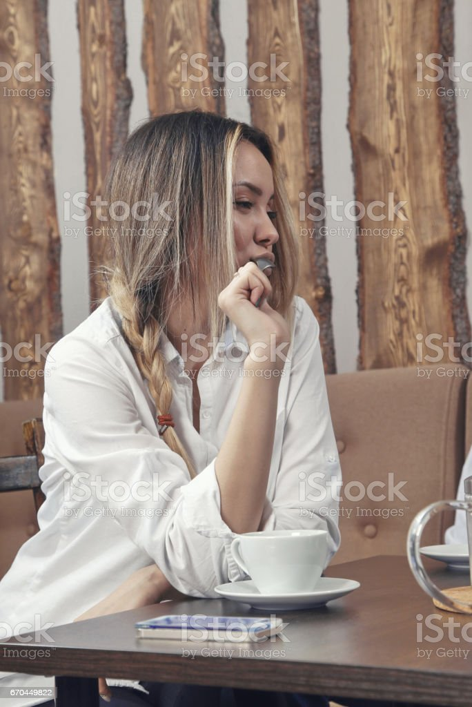 A young girl drinks coffee at a table in a cafe on which the phone lies and hold the spoon in the mouth stock photo