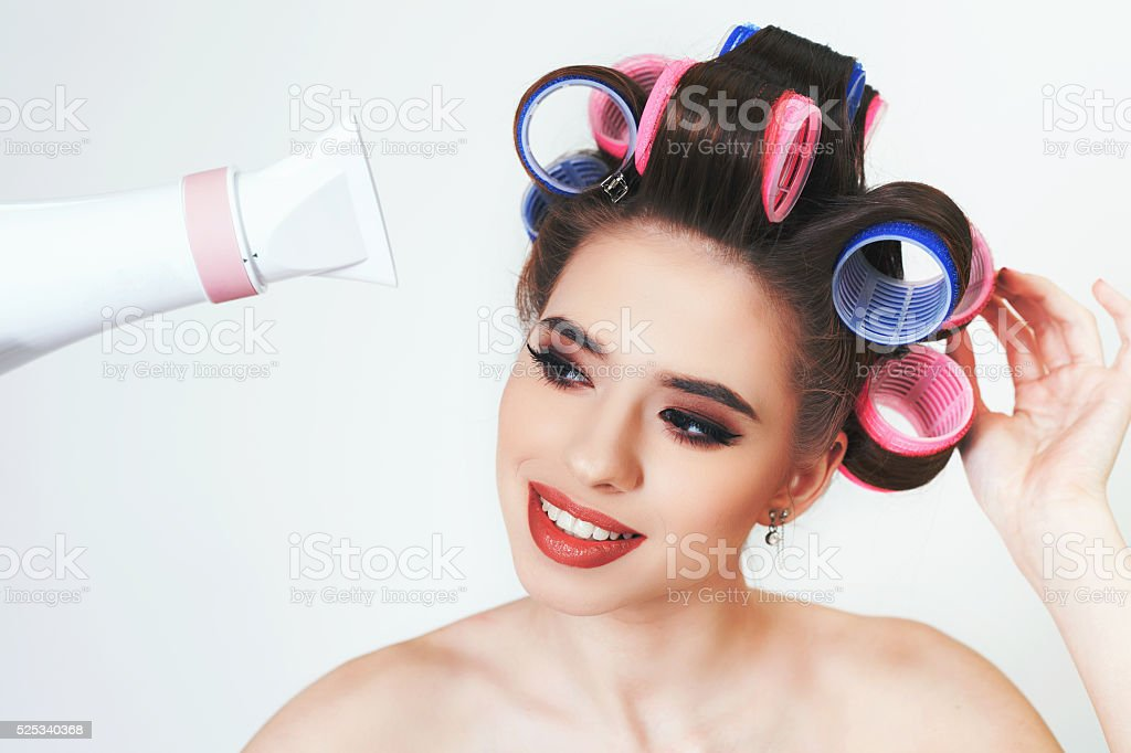 Young girl drying hair by hairdryer stock photo