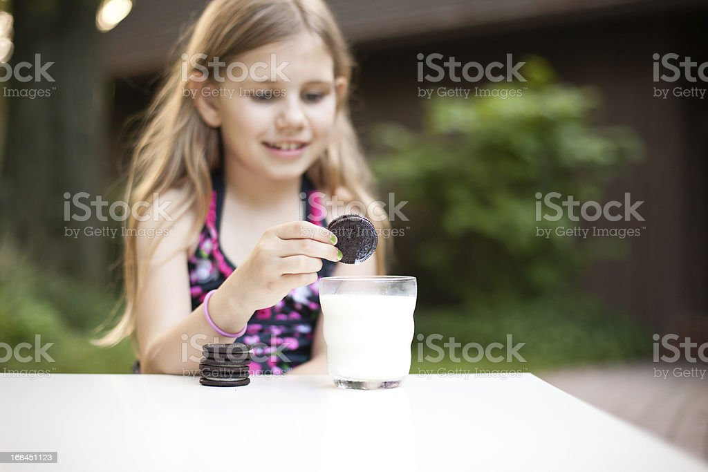 Young Girl Dunking Her Cookie in Milk royalty-free stock photo
