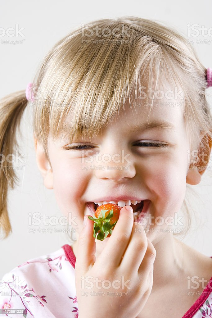 Young girl eating a strawberry royalty-free stock photo