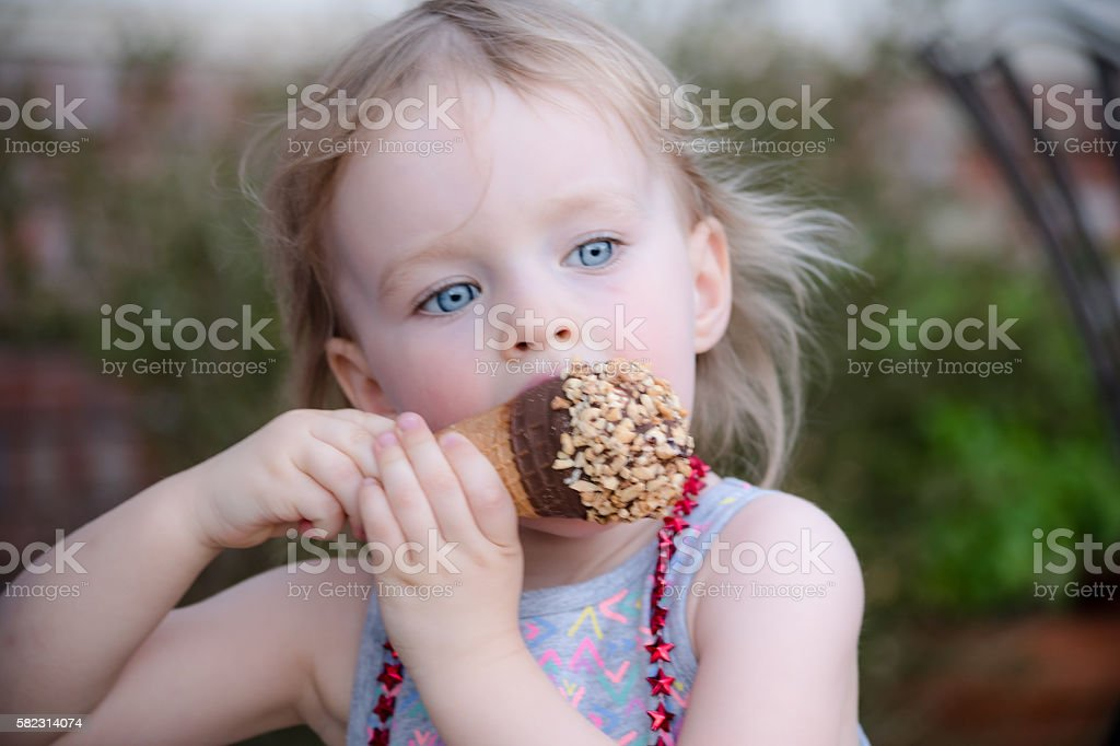 Young Girl Eating Ice Cream on the 4th of July stock photo