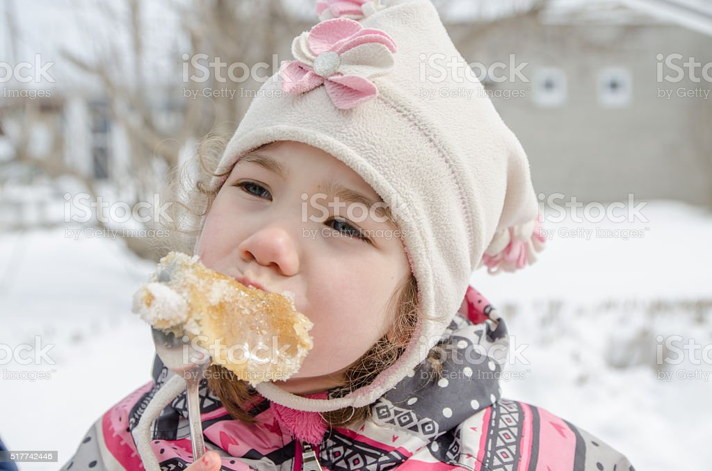 Young girl eating maple syrup taffy outside stock photo