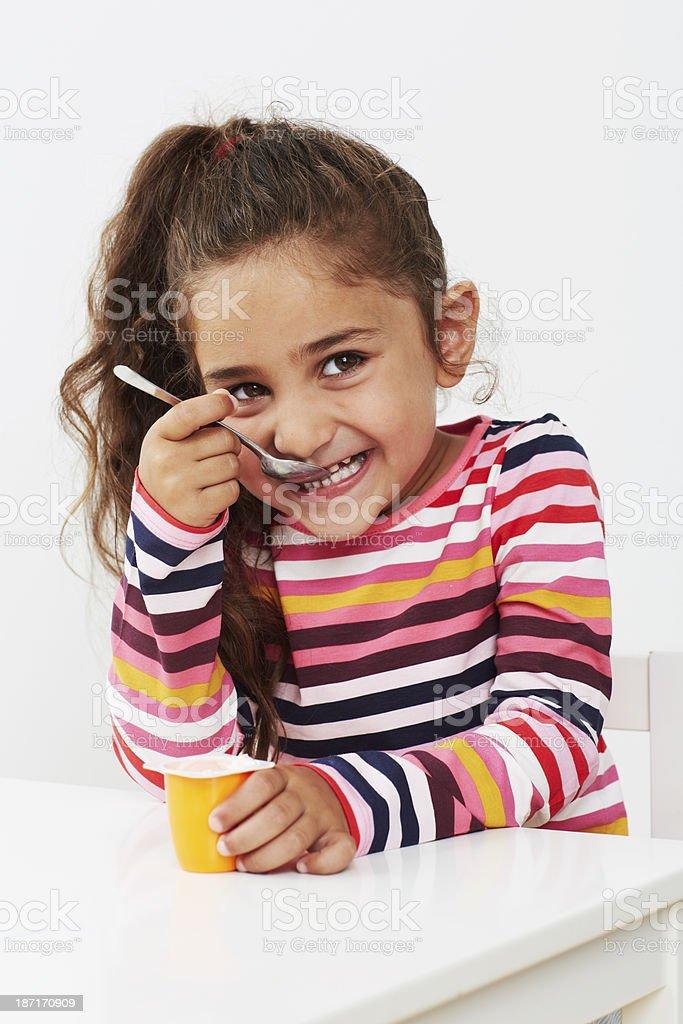 Young girl eating yoghurt in studio stock photo