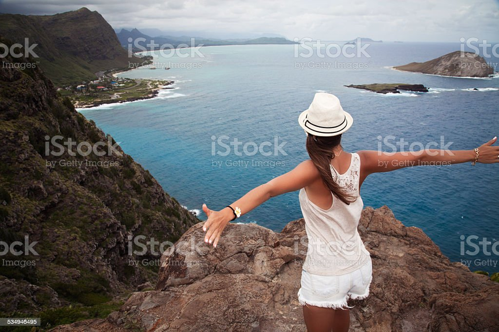 Young girl enjoying a valley view from top of a mountain stock photo