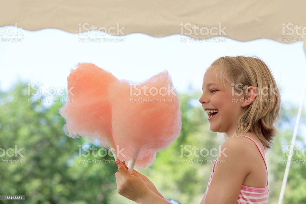 Young girl enjoying cotton candy stock photo