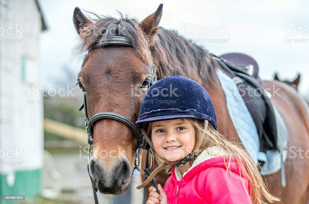 Young girl enjoying horse riding lesson stock photo