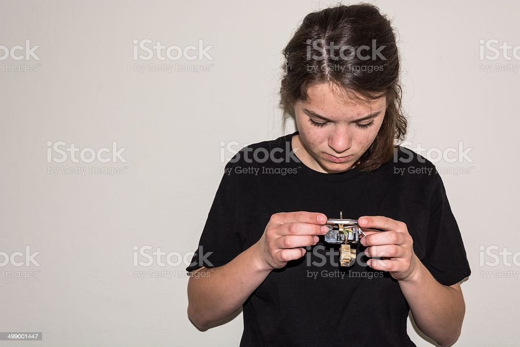 Young girl examinating a damaged electric socket stock photo