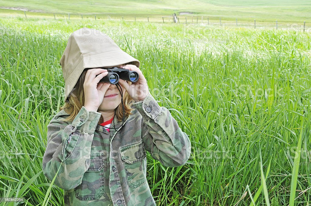 Young girl explores nature with binoculars stock photo