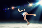 Young girl figure skating with spotlight on her