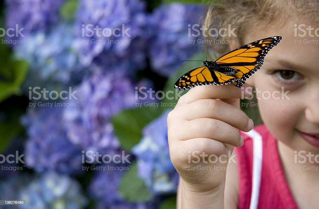 Young girl finding beauty in monarch butterfly on her finger royalty-free stock photo
