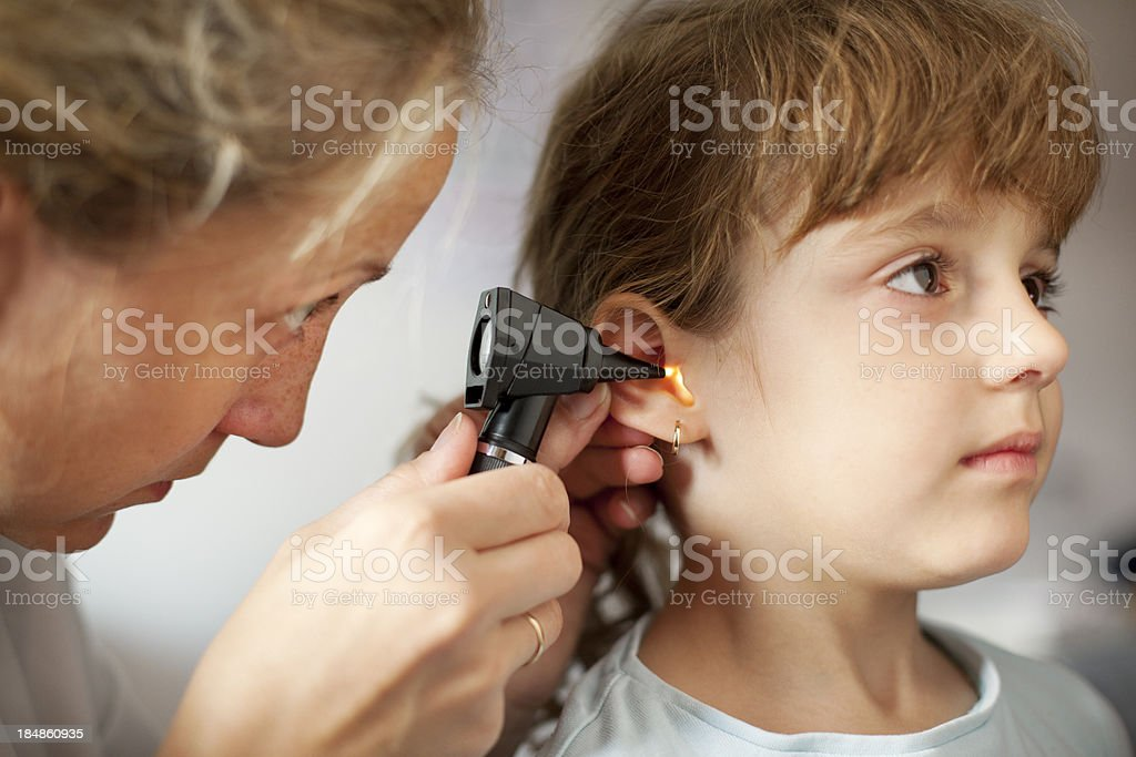 Young girl gets ear exam from pediatrician stock photo