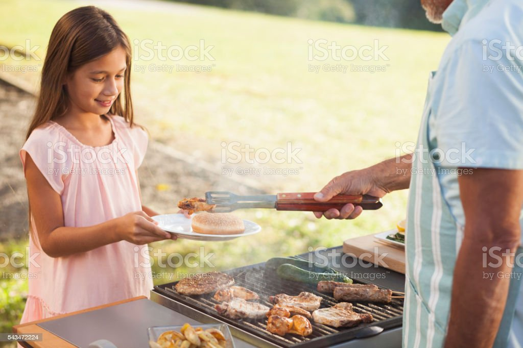Young girl getting her BBQ meat. stock photo